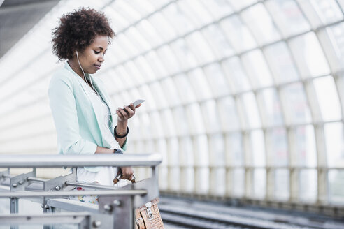 Young woman with earphones looking at her smartphone while waiting at platform - UUF007785