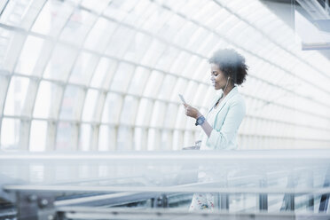 Young woman with earphones and smartphone waiting at platform - UUF007788