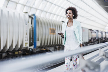 Portrait of smiling young woman with earphones and smartphone at platform - UUF007791