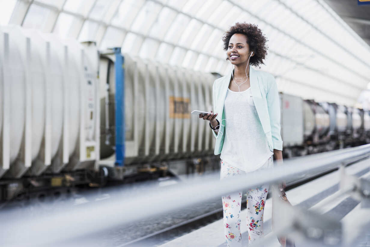 Portrait of smiling young woman with earphones and smartphone at platform - UUF007791 - Uwe Umstätter/Westend61