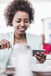 Portrait of smiling young woman in a cafe looking at her smartphone - UUF007794