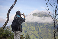 Indonesia, Java, Woman hiking in mountains and taking pictures with smart phone - KNTF000394