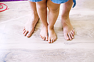 Bare legs of father and daughter standing on wooden floor - HAPF000509