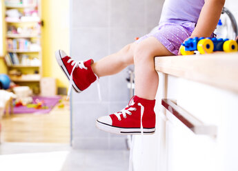 Little girl sitting in kitchen with read canvas shoes - HAPF000518
