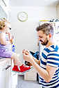 Father putting his daughter shoes on - HAPF000521
