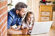 Father and daughter using laptop at home - HAPF000533