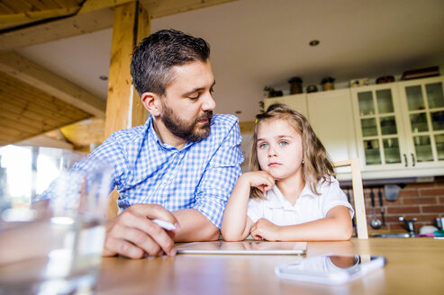 Father and daughter sitting at home using digital tablet - HAPF000539