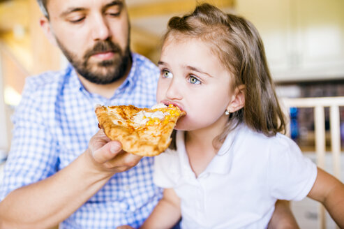 Father feeding his little daughter with pizza - HAPF000542
