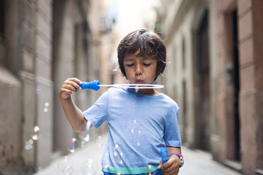 Little boy blowing soap bubbles in the street - VABF000639