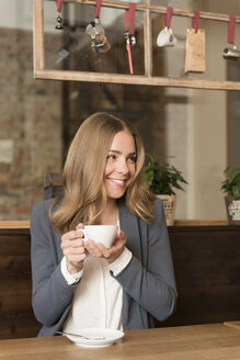 Portrait of happy young woman drinking coffee in a coffee shop - KAF000157