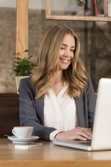 Portrait of smiling young woman using laptop in a coffee shop - KAF000160