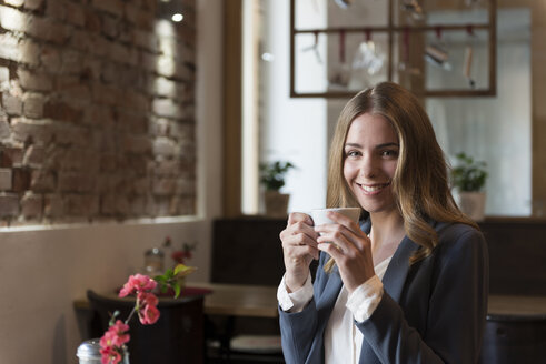 Portrait of smiling young woman drinking coffee in a coffee shop - KAF000163