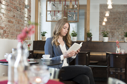 Young woman reading book in a coffee shop - KAF000166