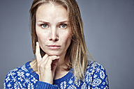 Portrait of serious blond woman with hand on chin - RHF001643