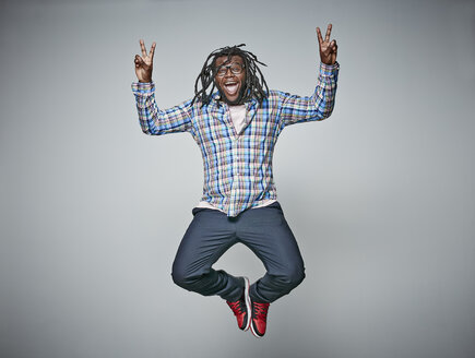 Screaming man with dreadlocks jumping in the air while showing victory signs - RHF001676