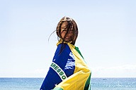 Young brunette woman playing with Brazilian flag at the beach - VABF000645