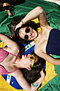 Two friends wearing beachwear, lying on Brazilian flag - VABF000648