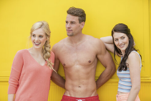 Portrait of man in trunks between two women in front of yellow background - GDF001018