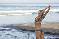 Indonesia, Bali, female surfer stretching at the beach - KNTF000402