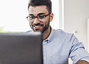 Smiling businessman with laptop in office - UUF007885
