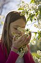 Little girl smelling blossoms of a tree - SARF002796