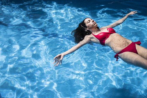 Woman floating on water of a swimming pool - ABZF000745