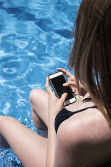 Woman sitting on the edge of a pool refreshing with her legs into the water using her phone, partial view - ABZF000751