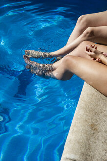 Legs of two women sitting on the edge of a pool - ABZF000757