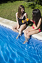 Two women sitting on the edge of a pool toasting with glasses of orange juice - ABZF000760