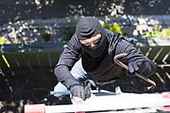 Burglar with crowbar climbing up ladder at house wall - MAEF011852