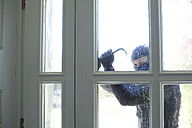 Burglar with crowbar breaking front door - MAEF011855