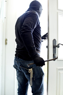 Burglar with pearl necklace in pocket leaving house - MAEF011867