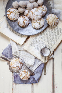 Home-baked Christmas cookies with powdered sugar on old book - SBDF002967