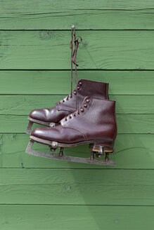 Vintage ice skates hanging in front of green wooden wall - KLRF000409
