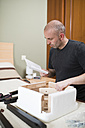 Man assembling furniture at home, reading instructions - RAEF001240
