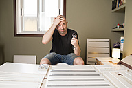 Man assembling furniture at home, looking desperate - RAEF001246