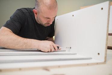 Man assembling furniture at home using screwdriver - RAEF001252