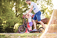 Father and little daughter together on a scooter - HAPF000547