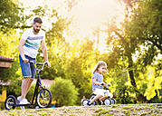 Father and his little daughter with toy car and scooter in a park - HAPF000556