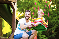 Portrait of happy father with his little daughter sitting on a swing of playground - HAPF000559