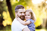 Portrait of happy father holding smiling little daughter on his arms - HAPF000568