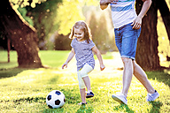 Happy little girl playing soccer with her father in a park - HAPF000571