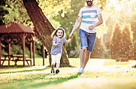 Portrait of smiling little girl running with her father hand in hand in a park - HAPF000577