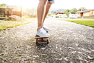 Legs of a man standing on skateboard - HAPF000589