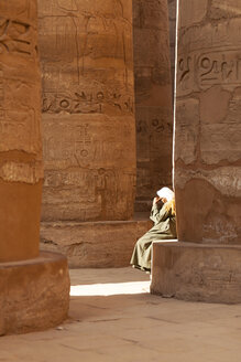 Egypt, Luxor, Karnak Temple, man sitting on column - FP000086