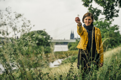 Germany, Cologne, happy woman standing on a meadow showing plant - DASF000055
