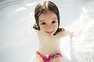Portrait of smiling little girl in a paddling pool - JASF000858