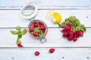 Glass of pickled red radishes and ingredients on wood - LVF005048