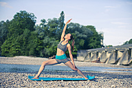 Woman practicing yoga by the riverside - YNF000007