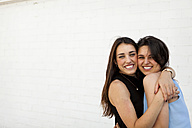 Two best friends hugging each other in front of white wall - VABF000651